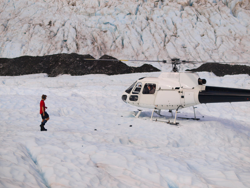 Helicopter on a glacier with man hiking towards it