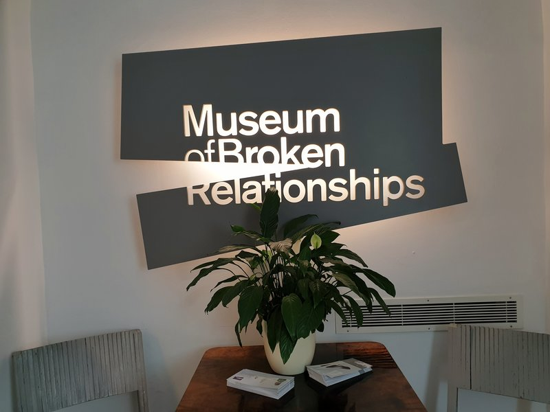 sign for the museum of broken relationships. the sign is broken and there's a pot plant in front of it